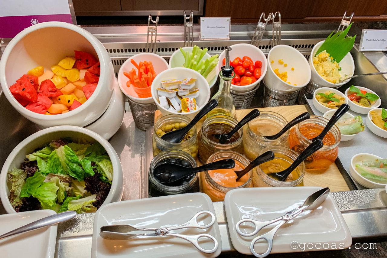 シェムリアップ国際空港のPLAZA PREMIUM LOUNGEのサラダコーナーに並ぶサラダと7種のドレッシング