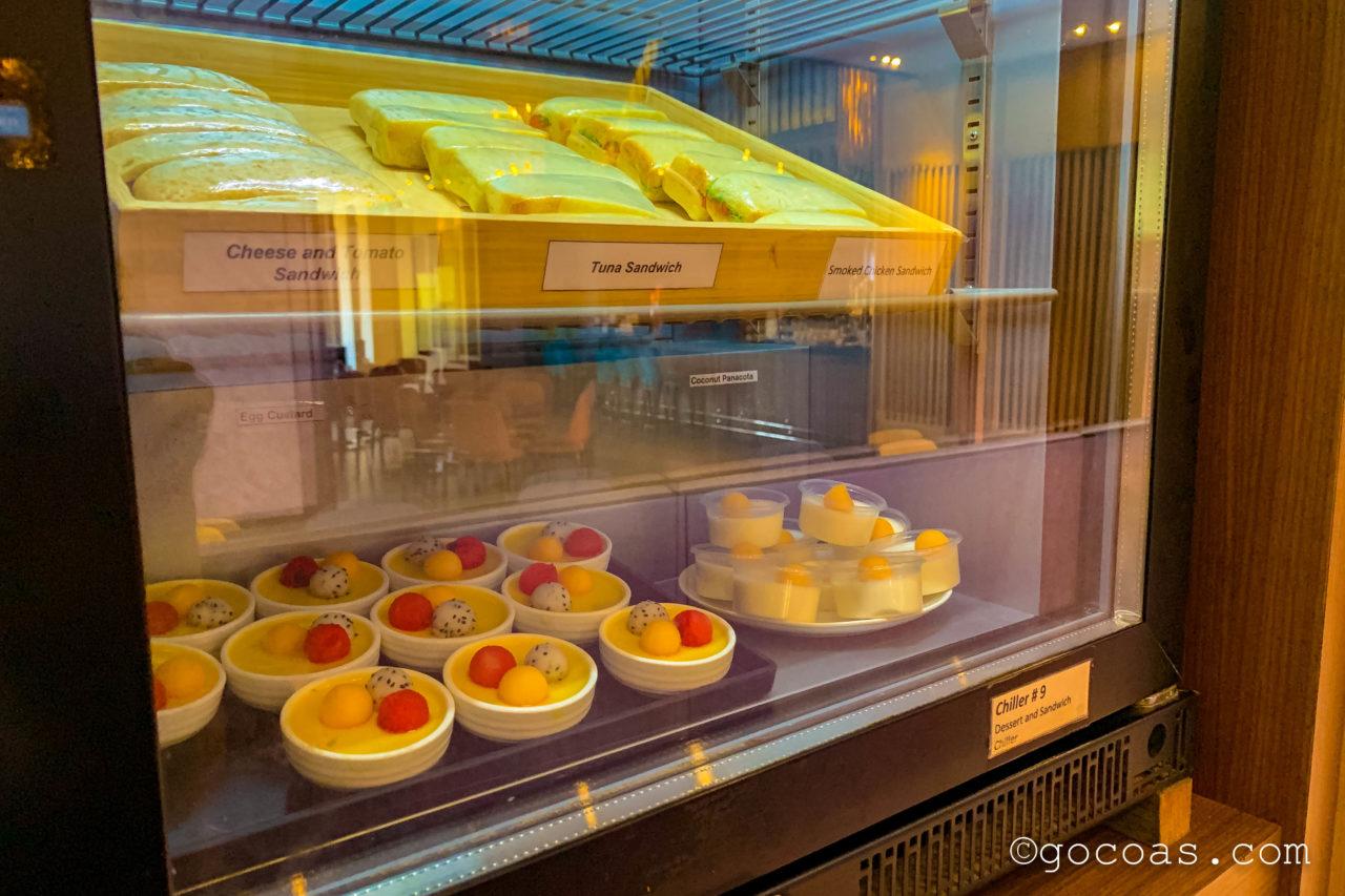 シェムリアップ国際空港のPLAZA PREMIUM LOUNGEのデザートコーナーにあるプリンのデザートとサンドイッチ
