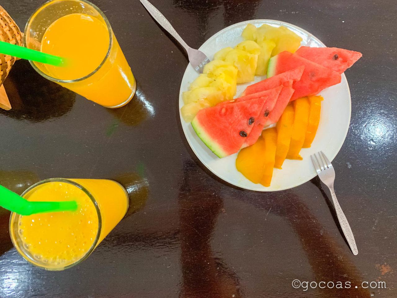 ルアンプラバーンホテルの朝食のジュースとフルーツプレート