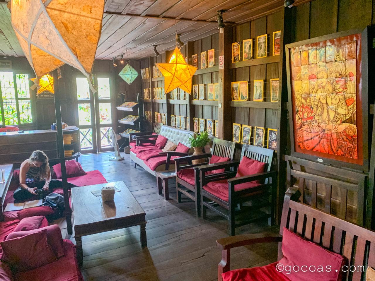 L'Etranger Books & Teaの店内に並ぶ椅子とクッションに座る外国人女性