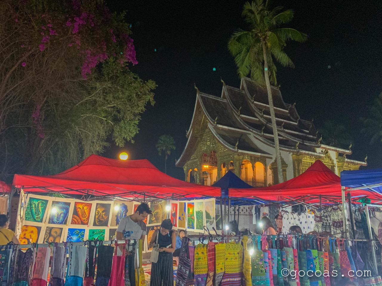 ルアンパバーンのナイトマーケットで並ぶお土産の屋台と寺院