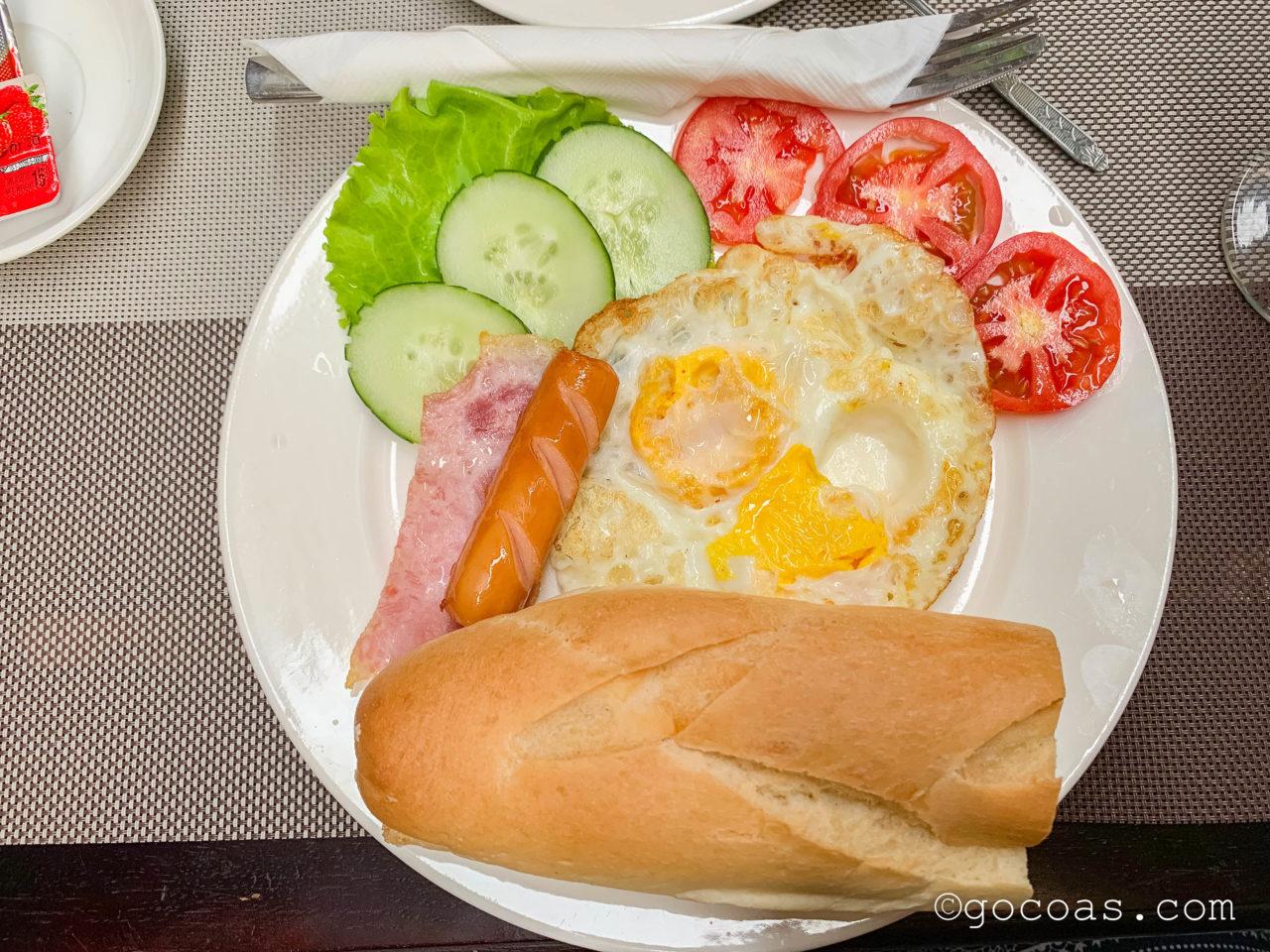 Villa Oudomlithの朝食のパンと卵とフルーツ