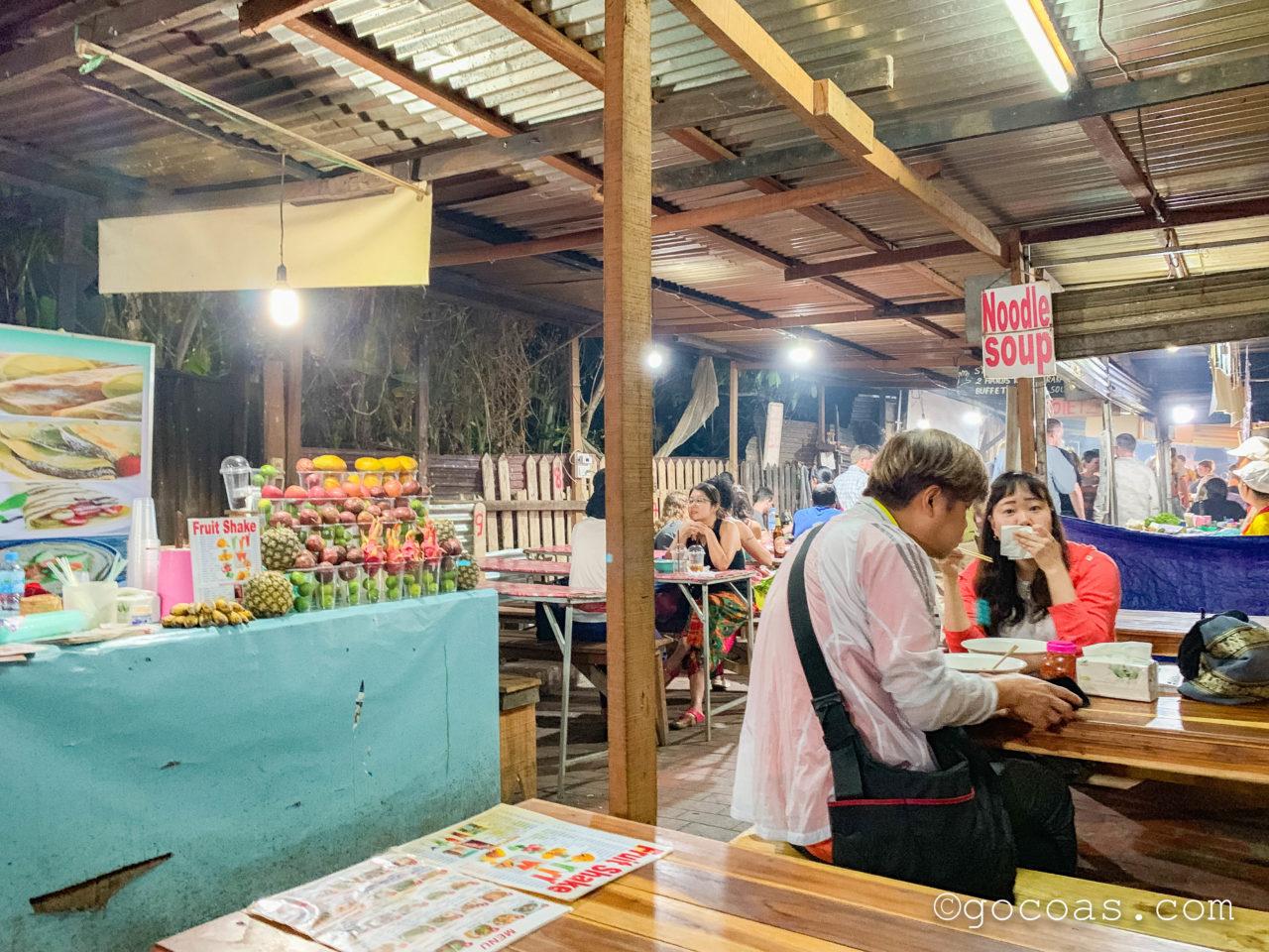 ルアンパバーンのナイトマーケットの飲食コーナーで並ぶテーブルに座る観光客とジュースの屋台