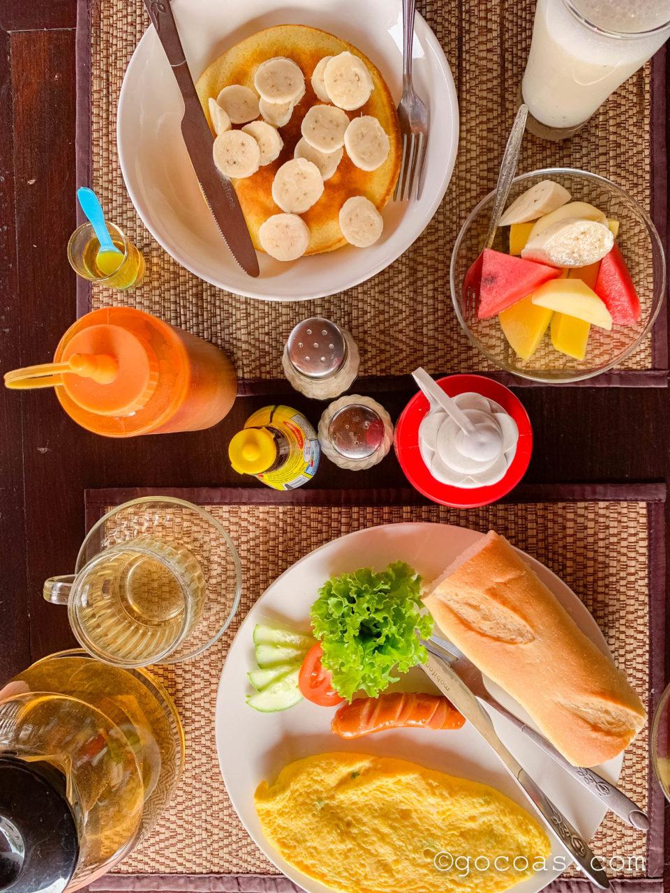 ヴィラ ラタナコンの朝食のパンケーキとパンと卵とフルーツ
