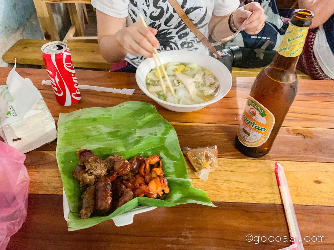 ルアンパバーンのナイトマーケットの飲食コーナーで食べたヌードルと串焼きとビアラオの瓶と缶コーラ