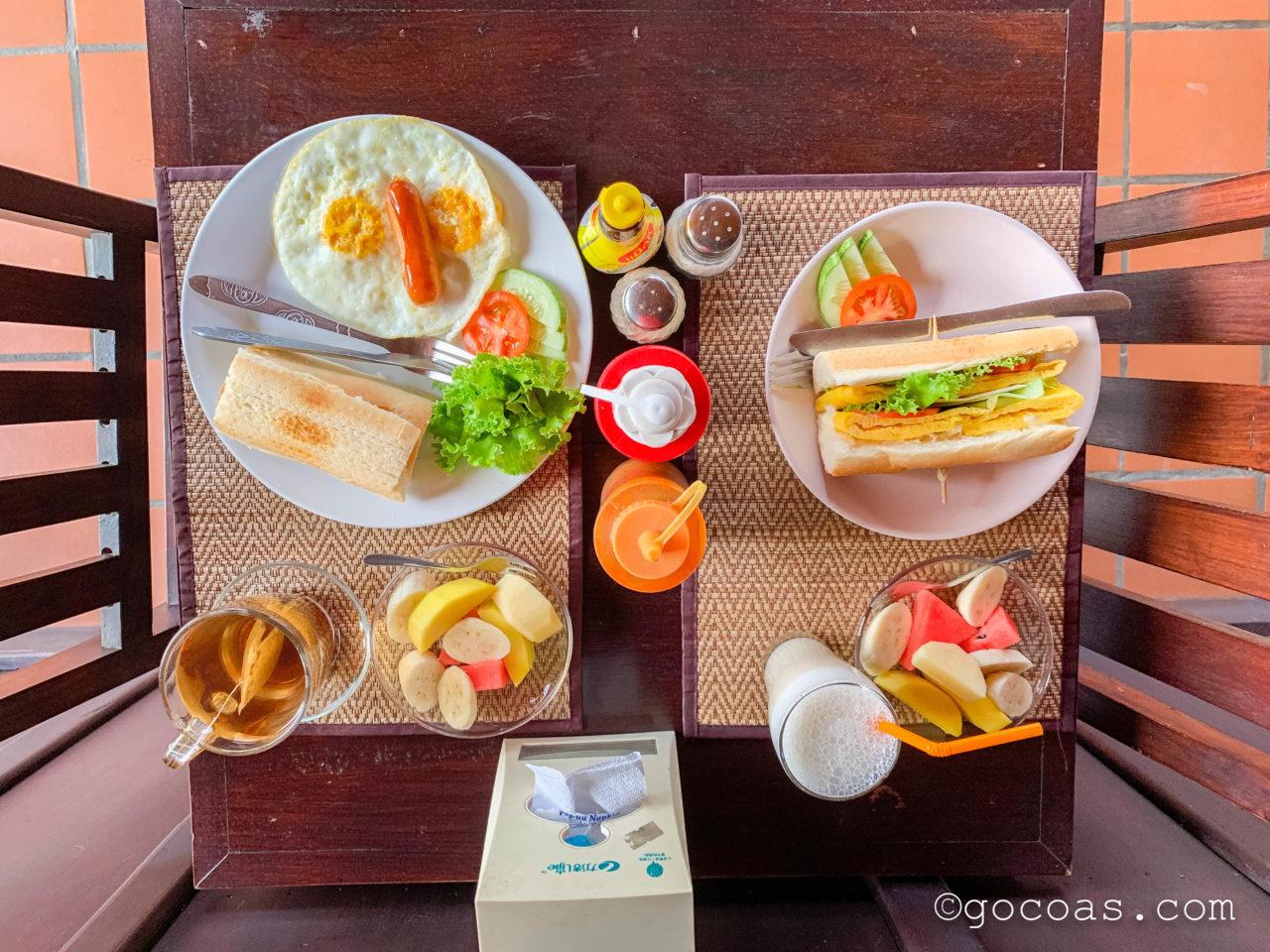 ヴィラ ラタナコンの朝食のサンドイッチとパンと卵とフルーツ