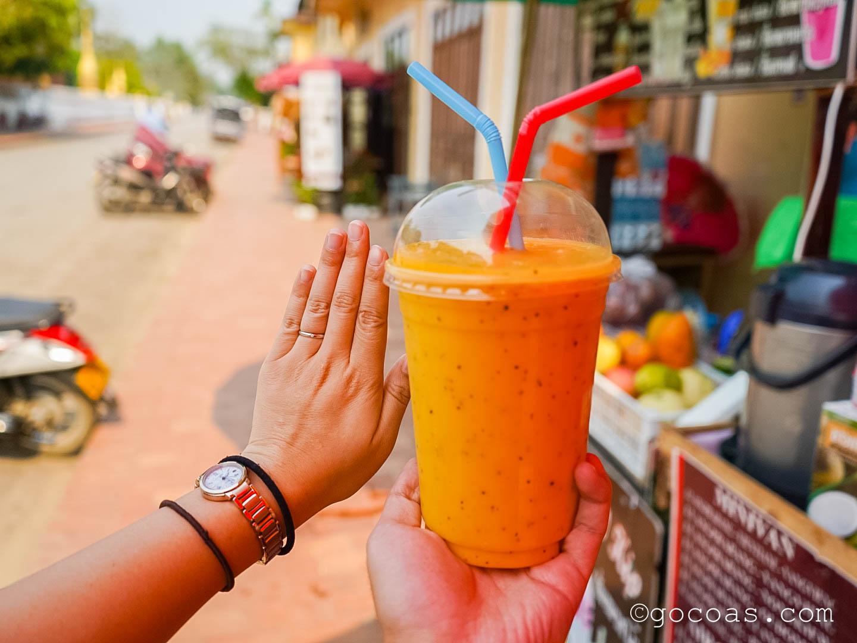 ルアンパバーンの街中の屋台で買ったフルーツジュースと手の比較
