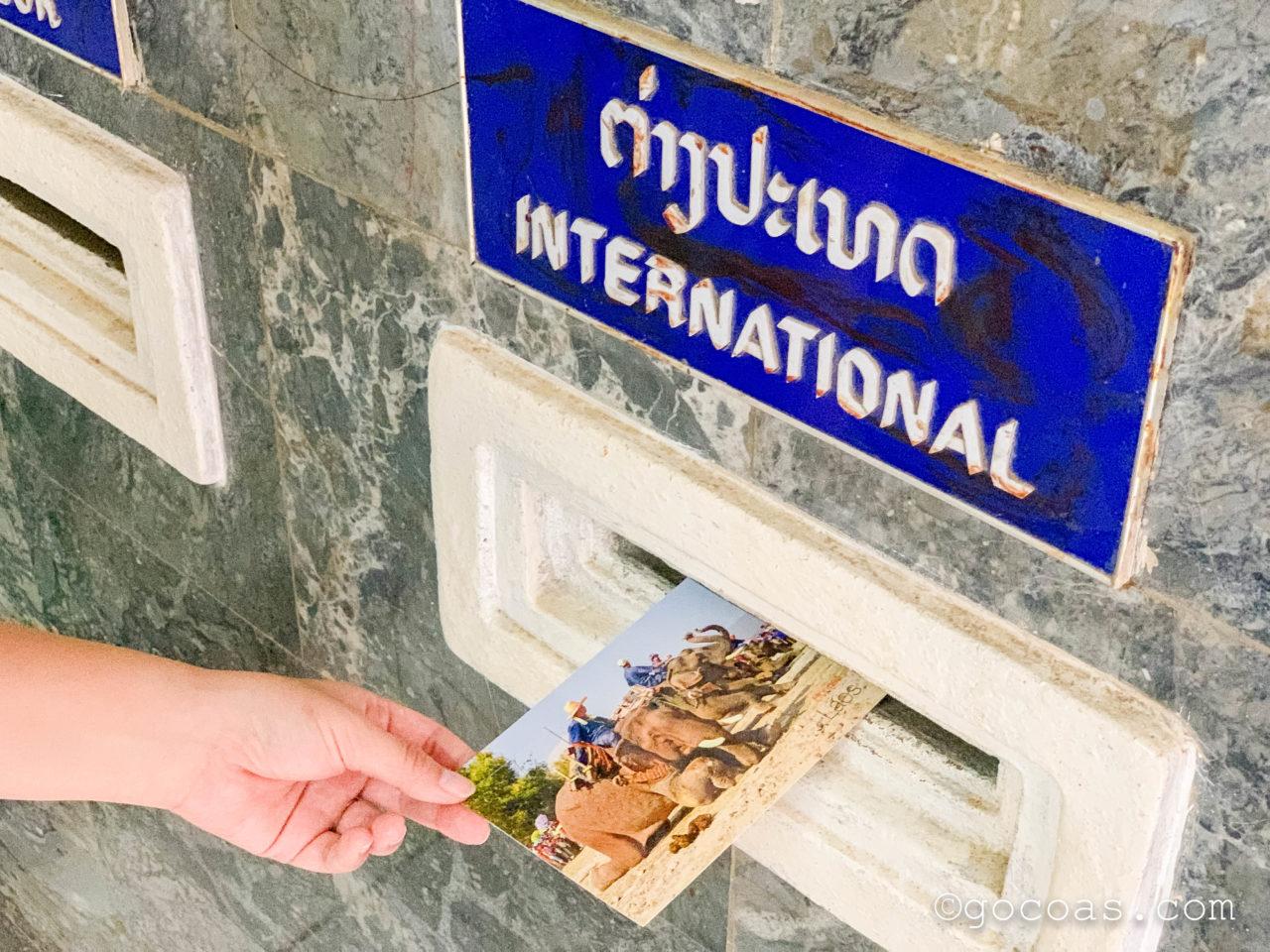 ルアンパバーンのポストカードを国際のポストに入れるところ