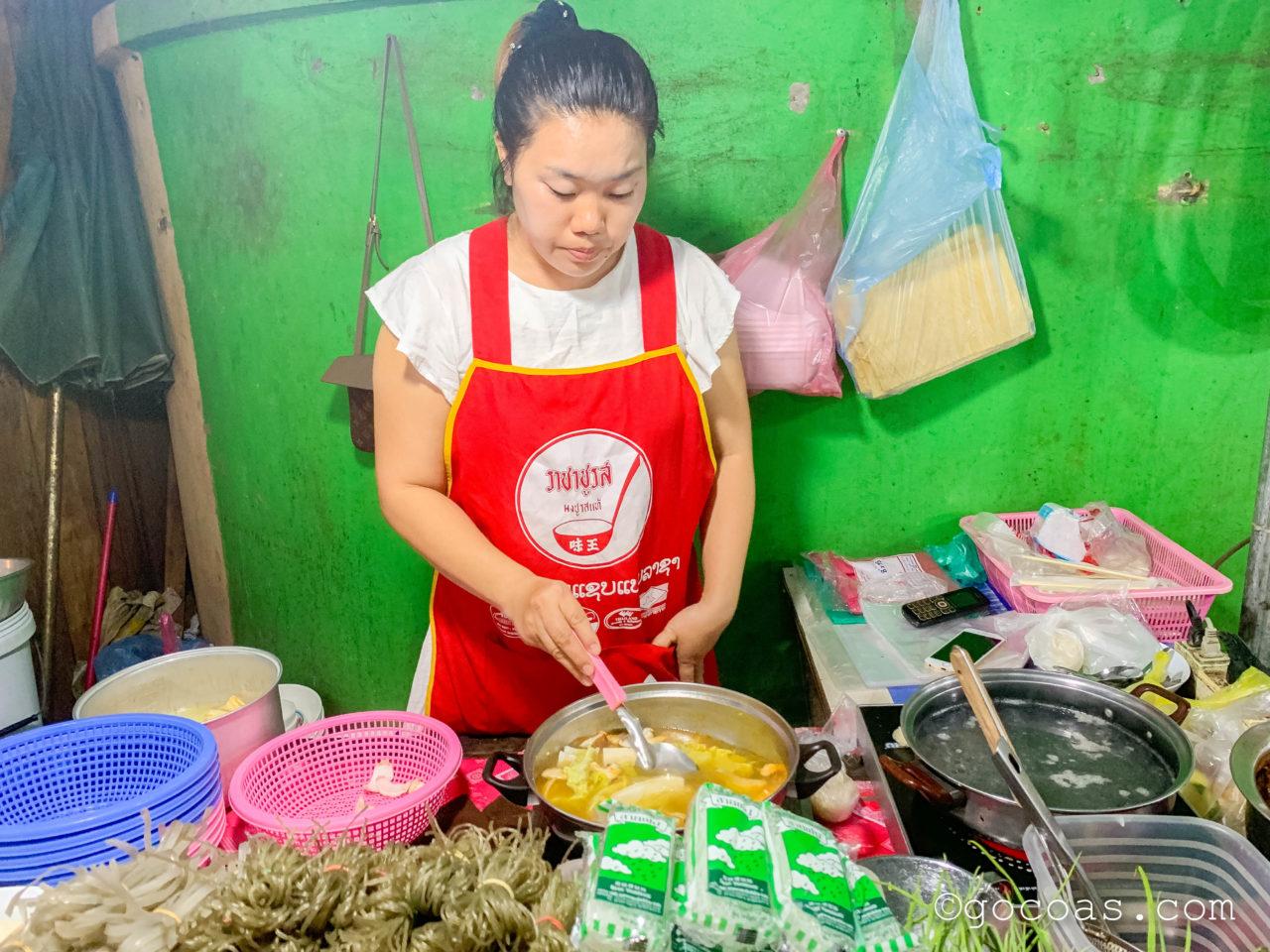 ルアンパバーンのナイトマーケットの飲食コーナーに並ぶ鍋の屋台でスタッフが調理しているところ