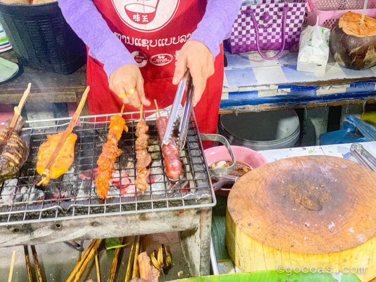 ルアンパバーンのナイトマーケットの飲食コーナーに並ぶ串焼きの屋台で注文した串を焼いてもらっているところ