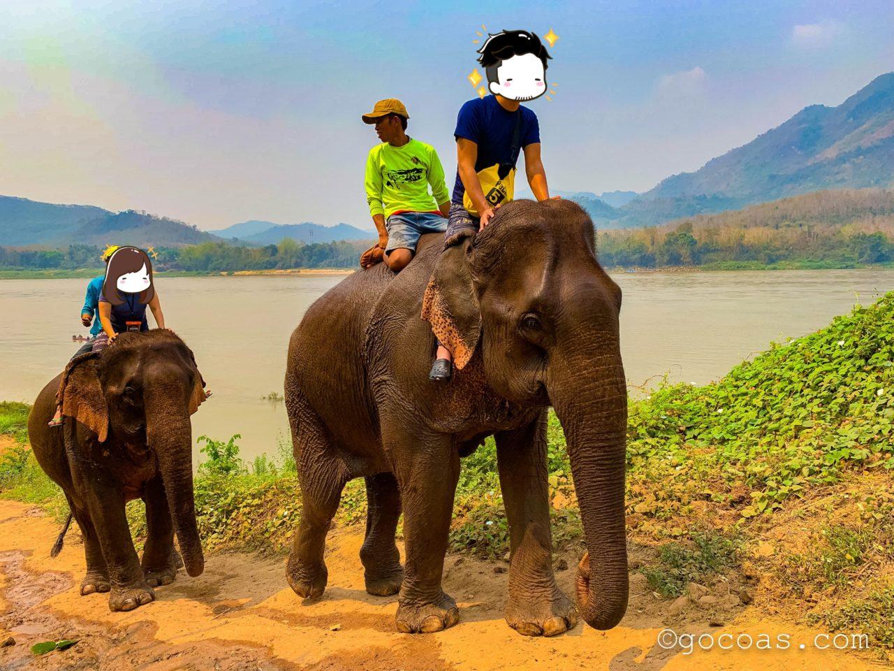 象使い体験で川で濡れた象に乗っているところ