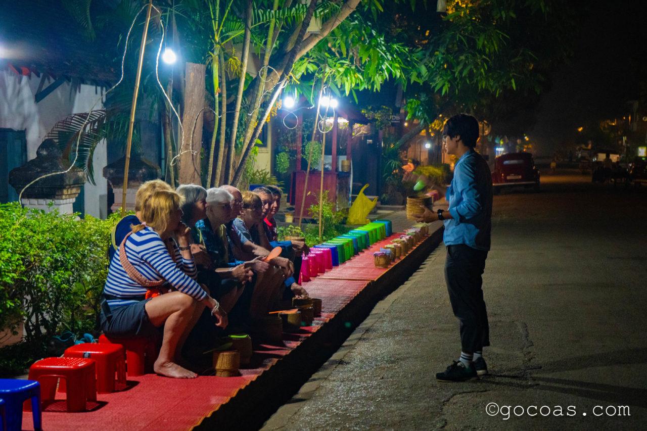 ルアンパバーンの托鉢で路上に並ぶ観光客とガイド