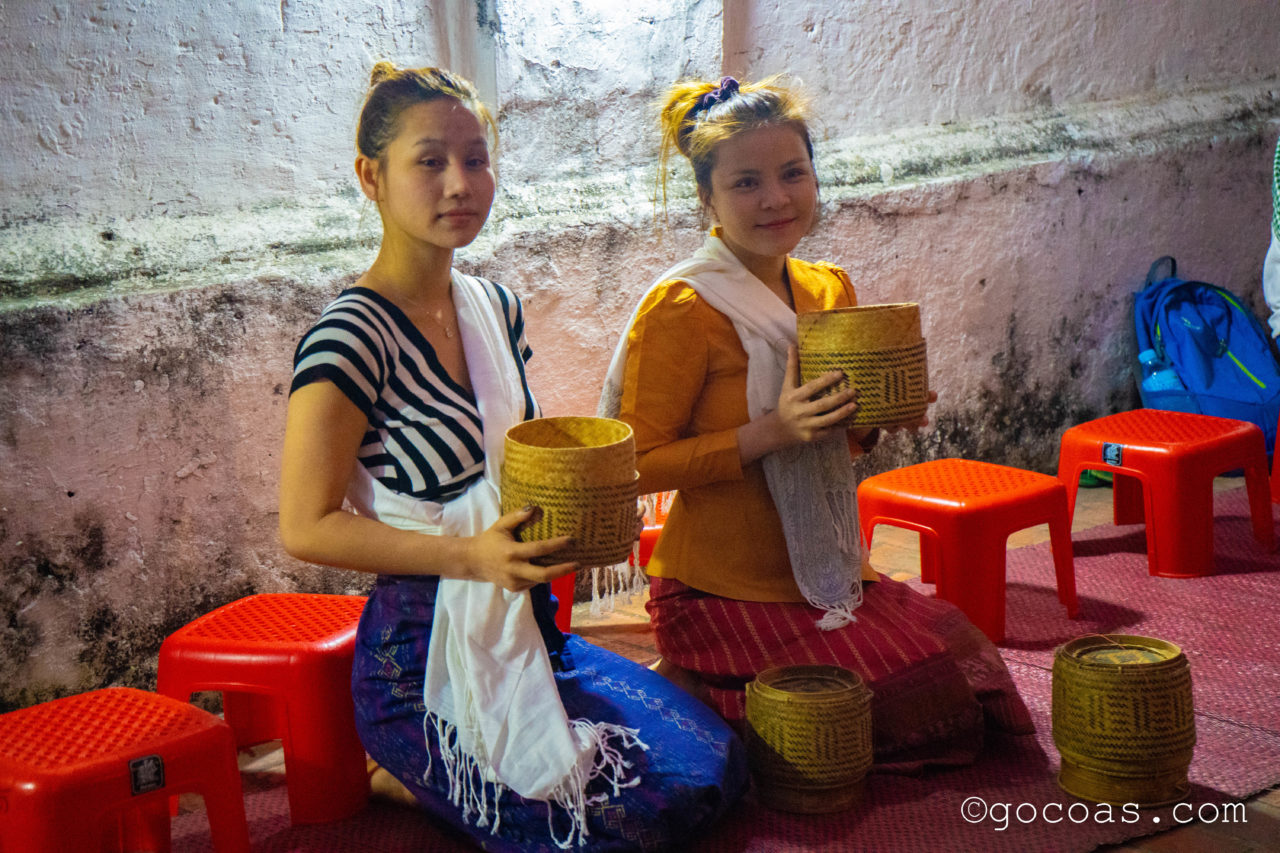 ルアンパバーンの托鉢でお米を渡す人