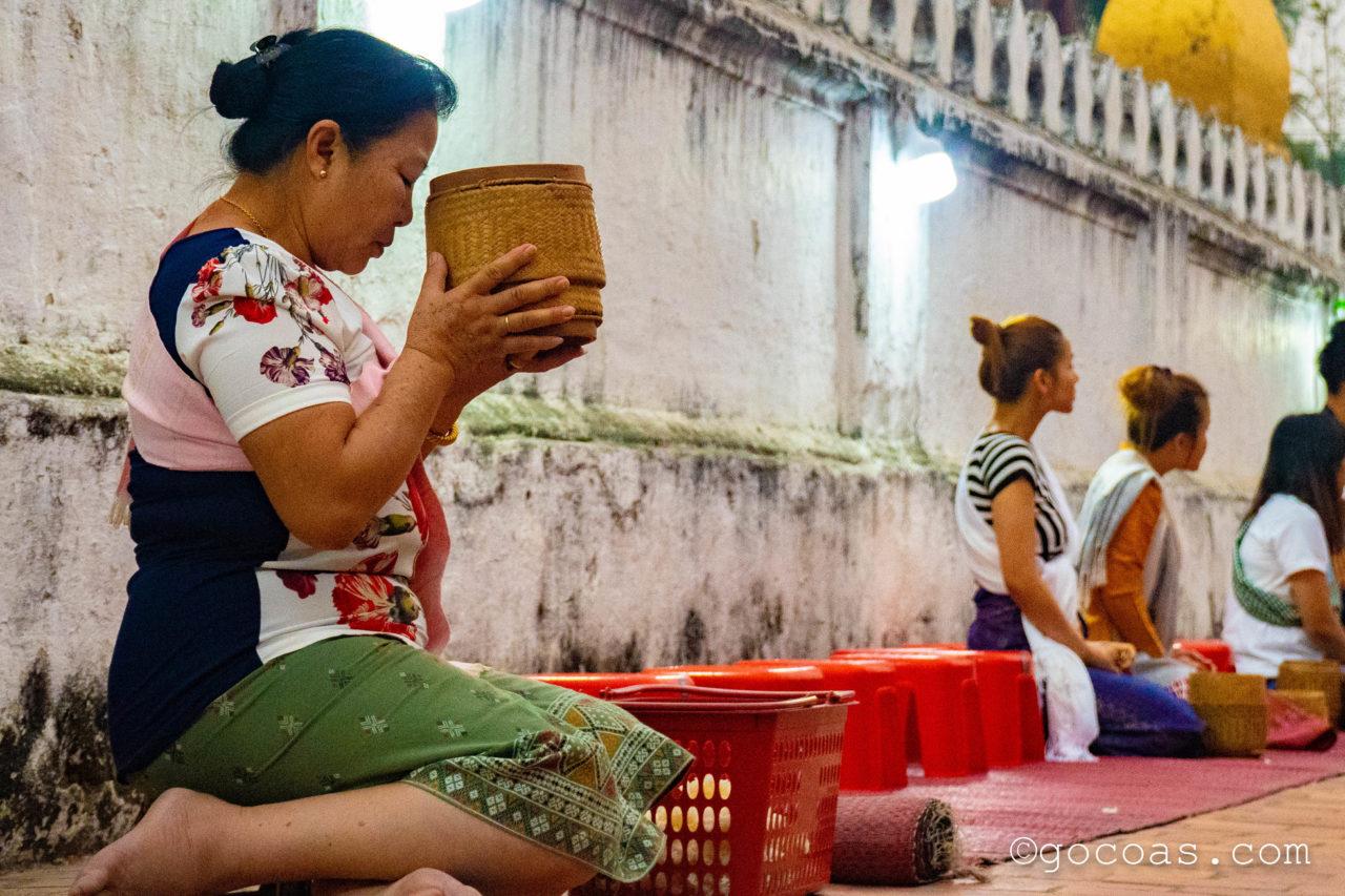 ルアンパバーンの托鉢でお祈りするお米を渡す人