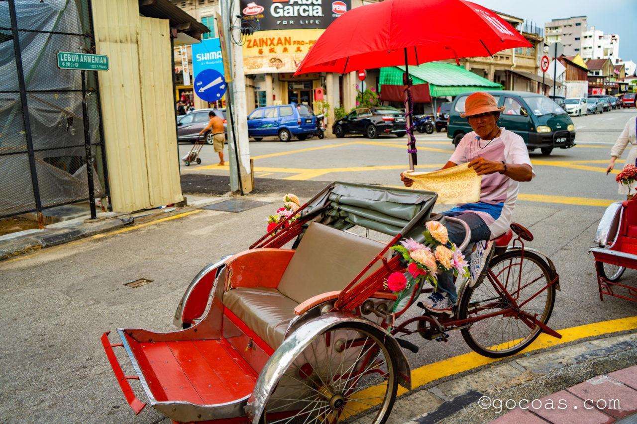 ペナン島の街中を走る人力車のおじさん