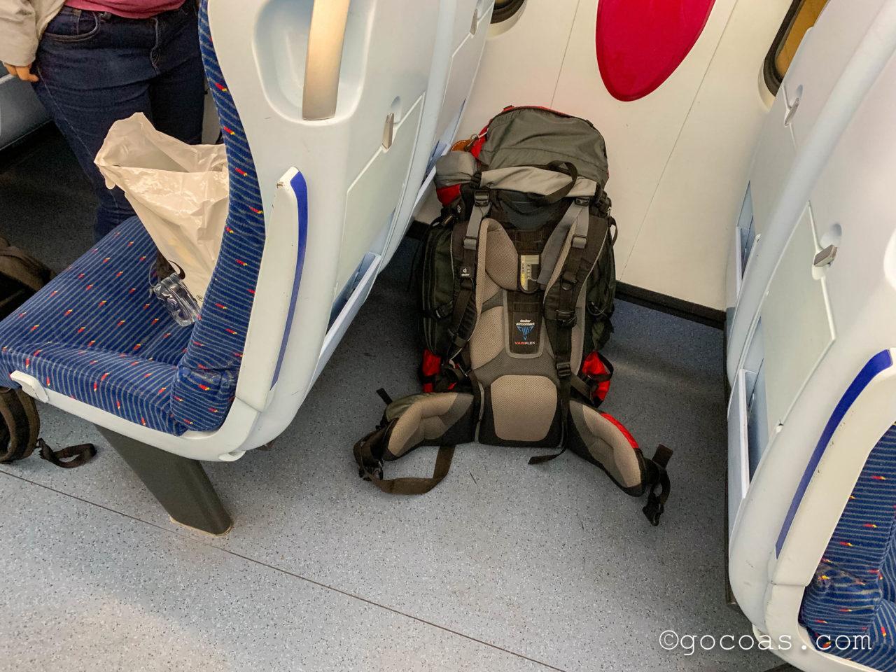 バタワース駅に来た電車内の座席の間にバックパックを置くところ