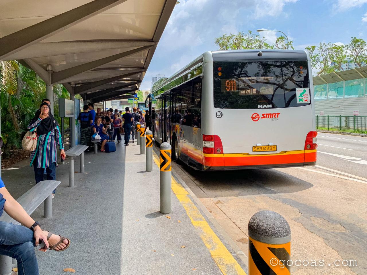 Woodlands Train Checkpointのバス停に停車しているバスと集まっている乗客